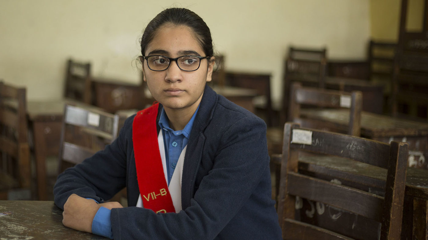 A girl with glasses sits in the classroom.