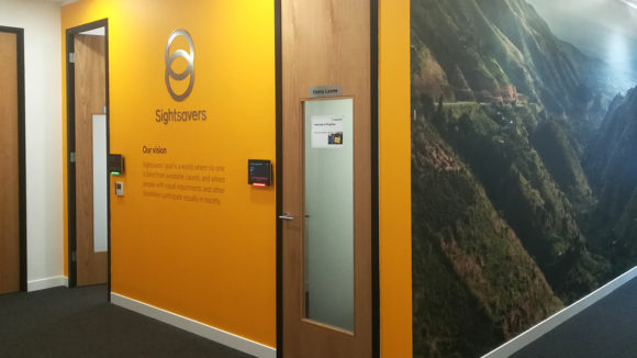 A Sightsavers office wall in yellow, featuring the logo and a large photo on the adjacent wall.