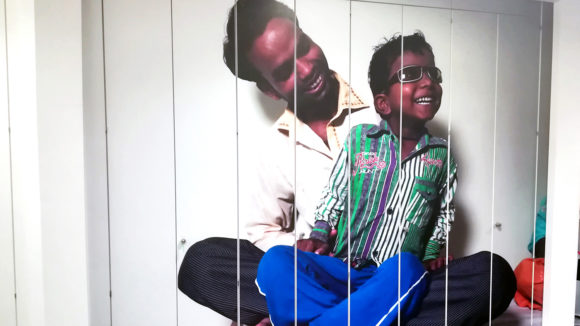 A photo of a man and his son on the front of some cupboards.