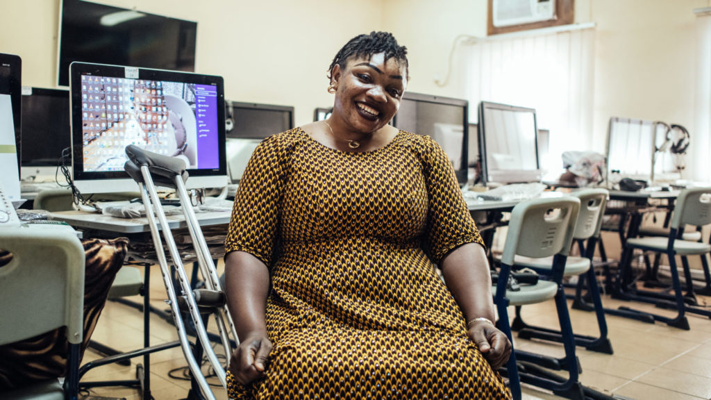 A women with crutches sits next to computers in an office smiling.
