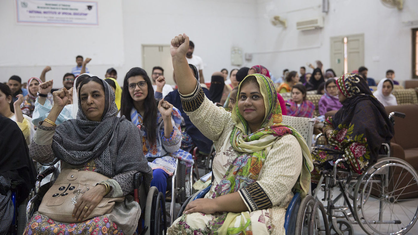 A group of people with disabilities raise their hands.