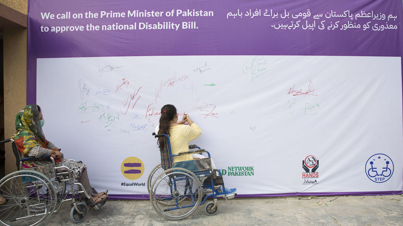 Two women in wheelchairs sign a petition on a wall.