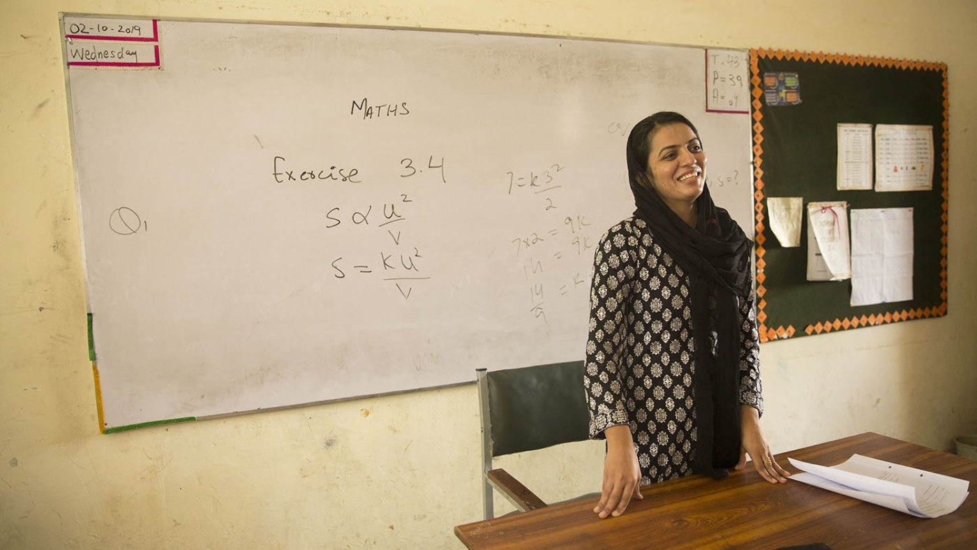 A teacher stands in front of a white board.