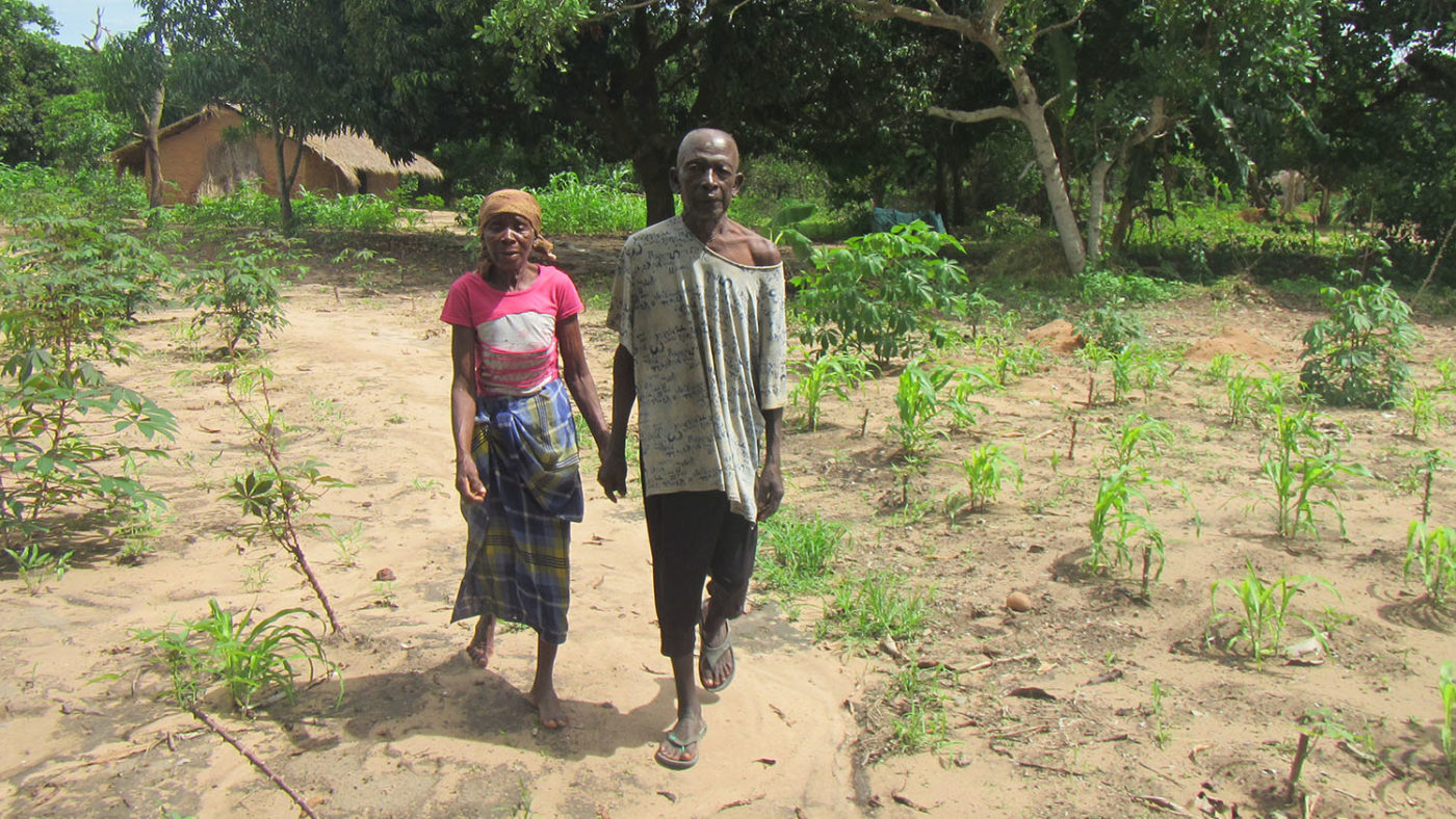 A man and a woman walk along a road holding hands.