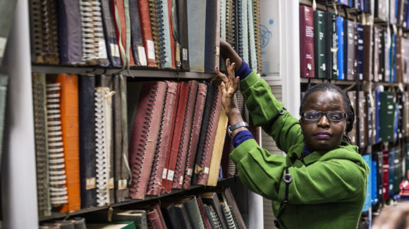 A women with visual impairment working in a library in Kenya.