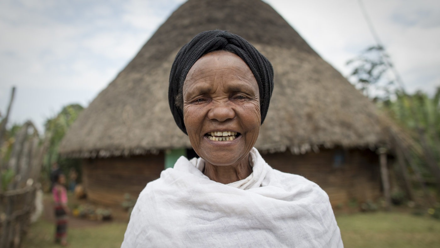 A lady smiles broadly at the camera with her home in Ethiopia in the distance behind her.
