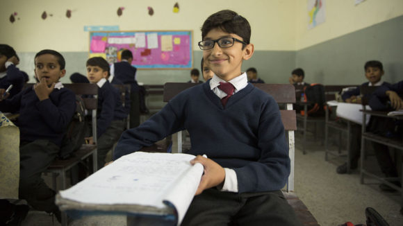 A boy wearing glasses smiling in the classroom.
