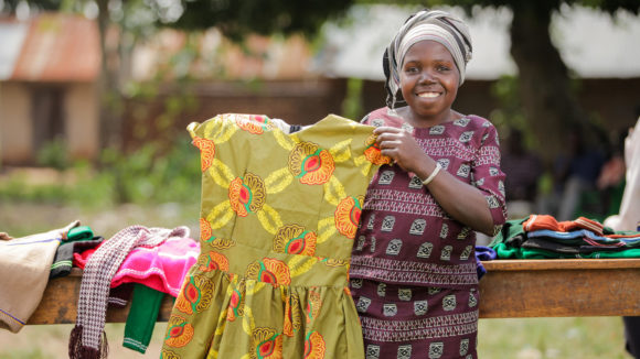 Aliango displaying a dress she made during the UN International Day of People with Disabilities in Kiryandongo town, Uganda.