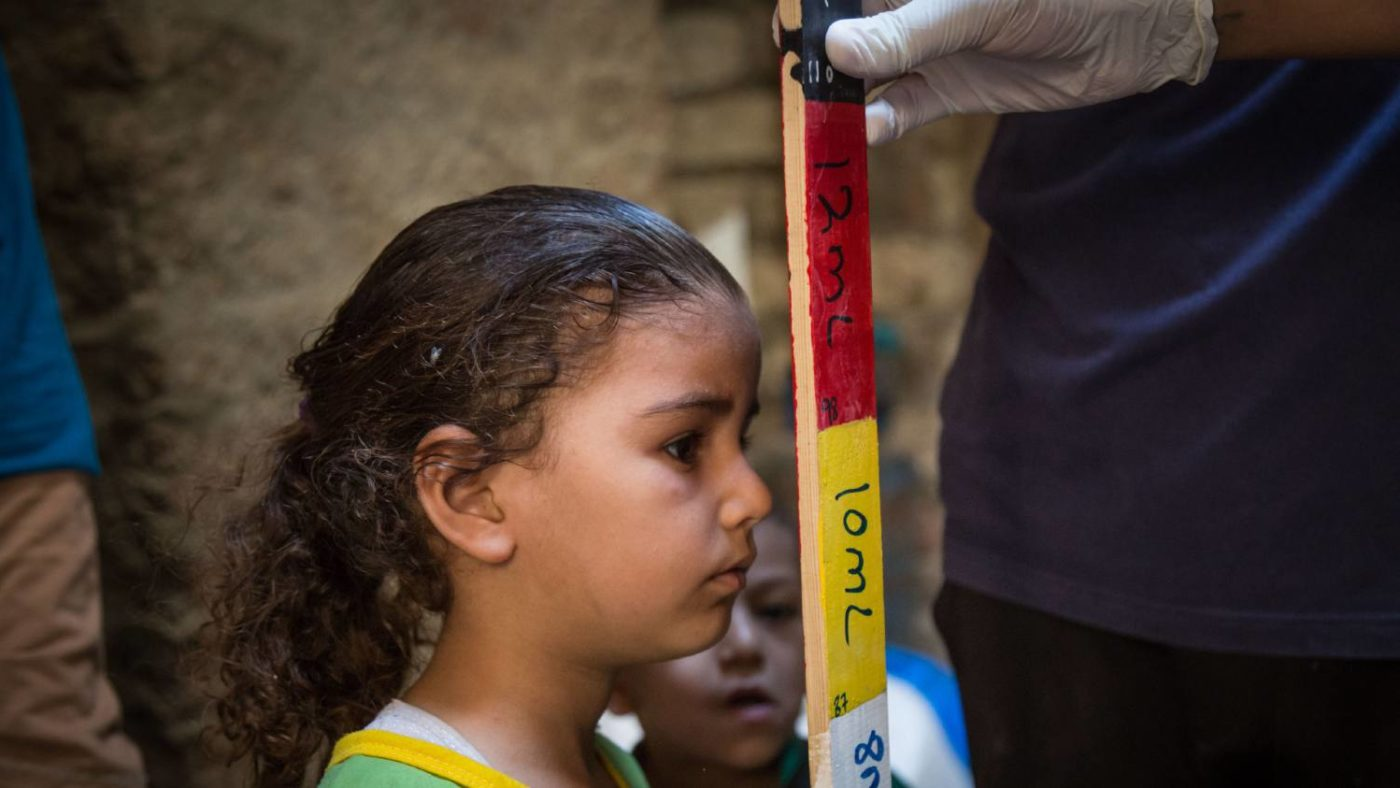 A young girl's height is measured using a colourful dose pole.