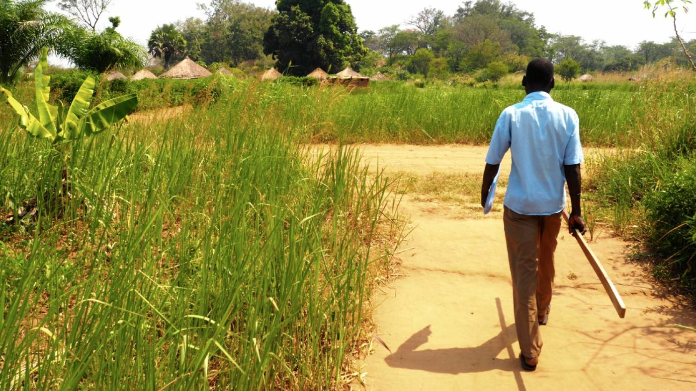 A community volunteer walks down a dirt road with his dose pole.