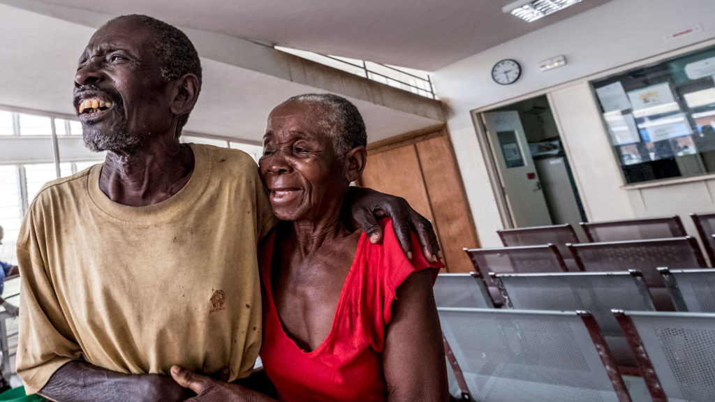 A man and woman embrace and smile in a hospital.