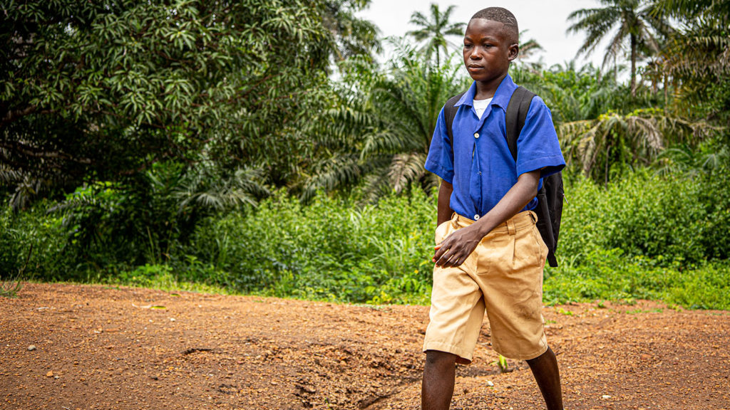 Abdul walks to school in his school uniform.