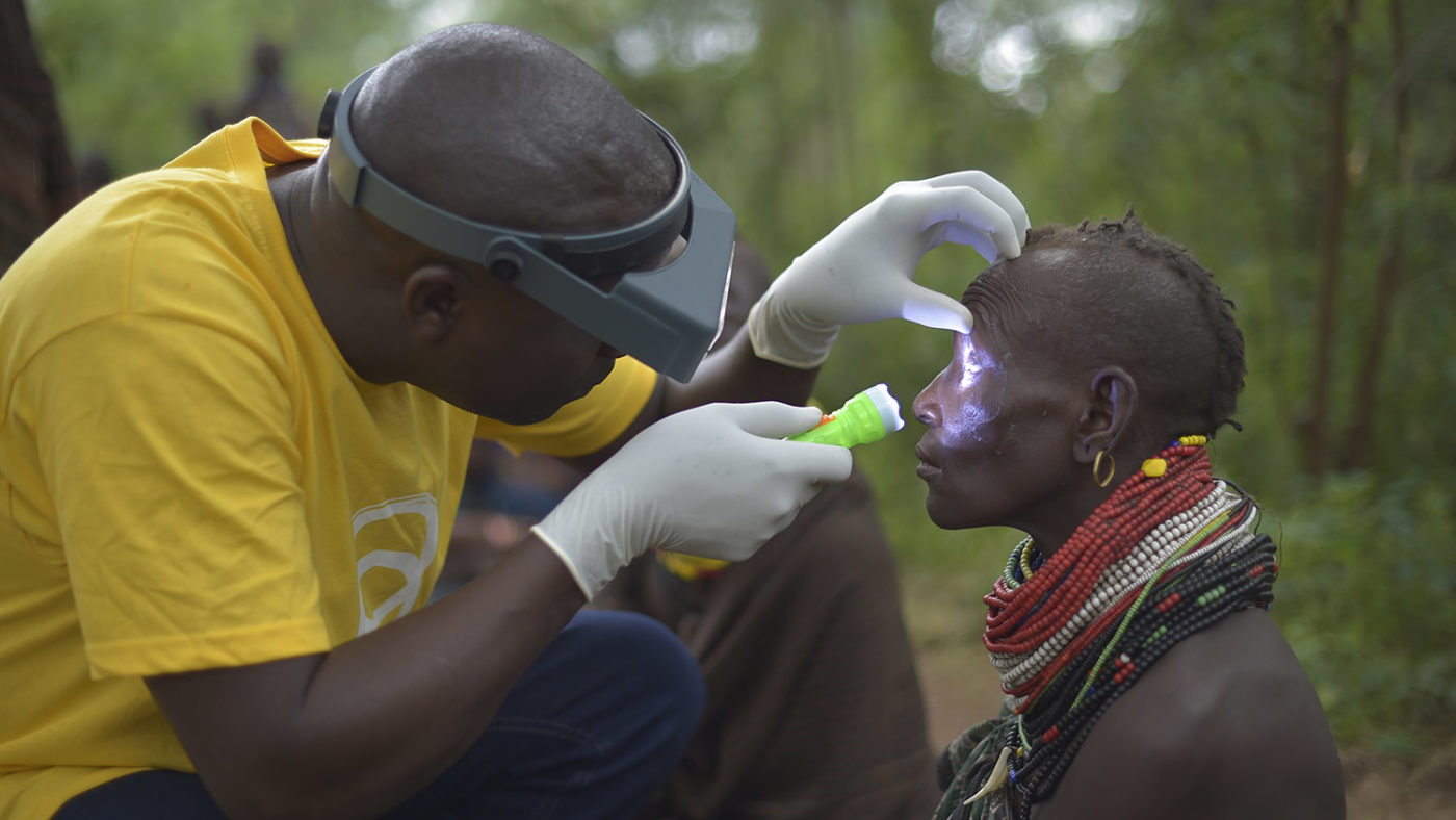 A health worker examines a woman's eye.