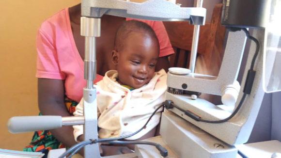 A little boy smiles after having an eye exam.