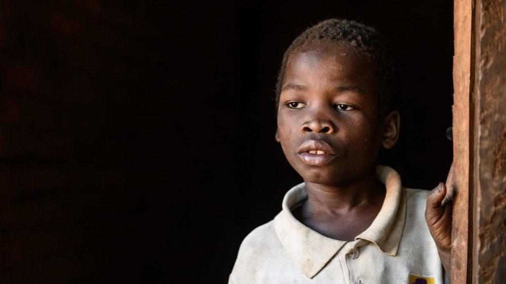 A boy looks sad as he looks outside.