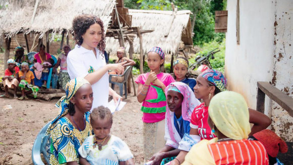 A woman speaks to a group of women and children seated outside,