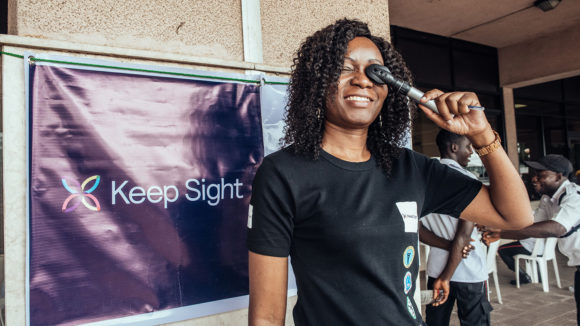 An eye health worker stood infront of a Keep Sight banner holds an eye examining instrument to her eye.
