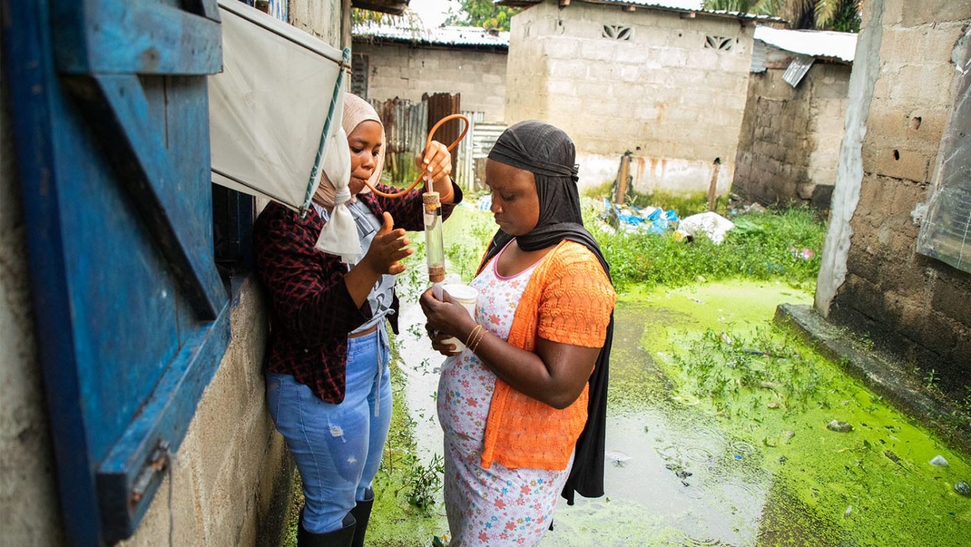 Two women are shown collecting mosquitoes using a trap.