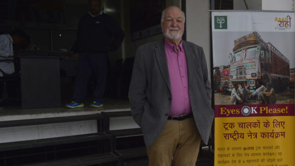 Clive Jones stands next to a sign.