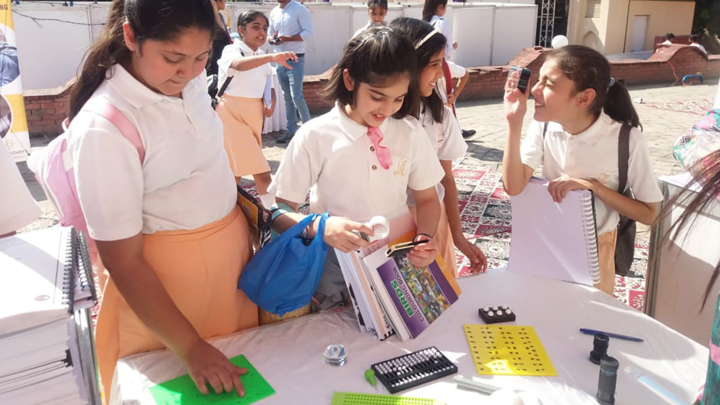 A group of children look at accessible reading materials.
