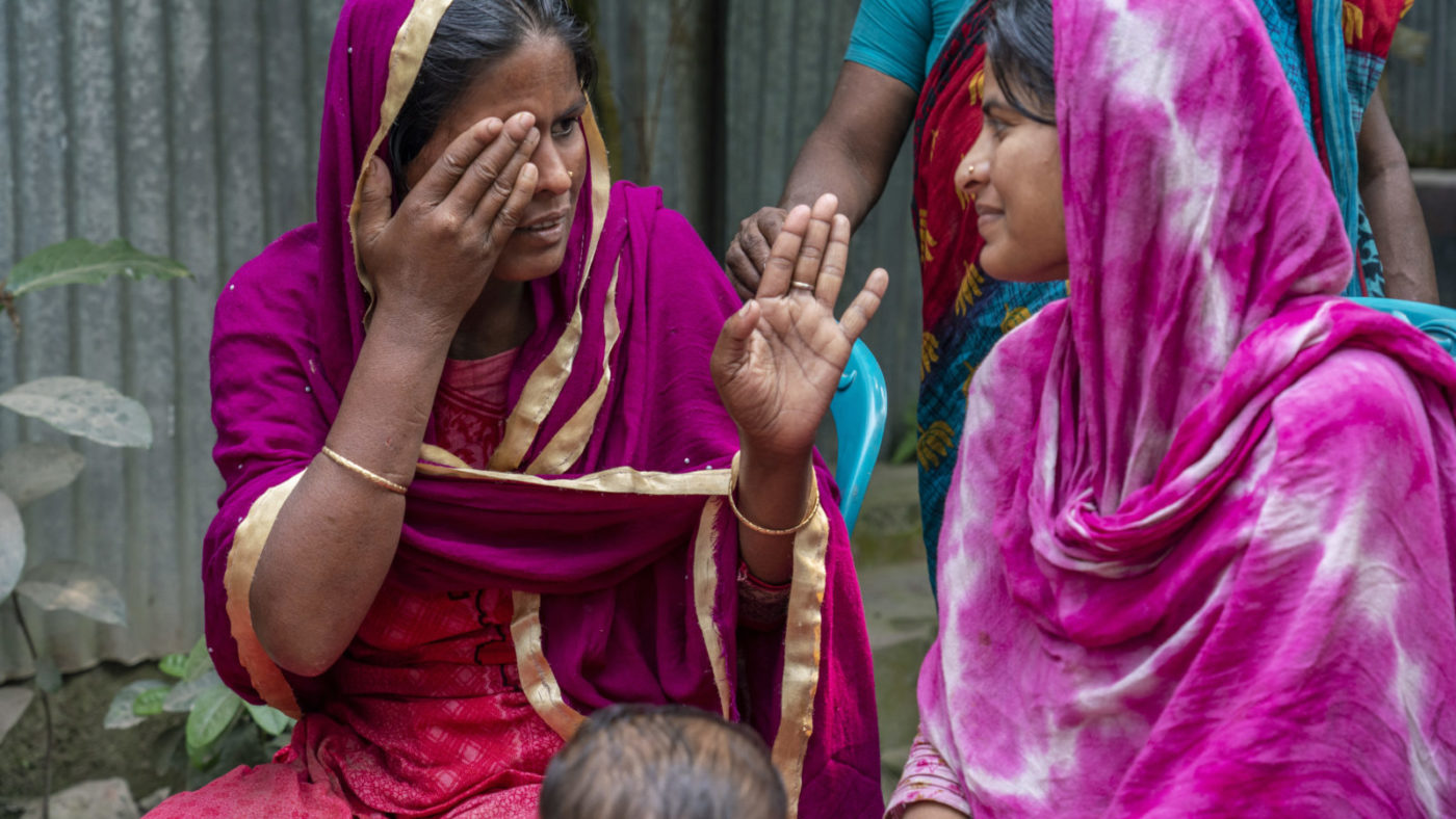 Shamima communicates with her sister. Her sister uses hand movements to get her point across. Both women are sitting down outside and wear bold, pink clothing.