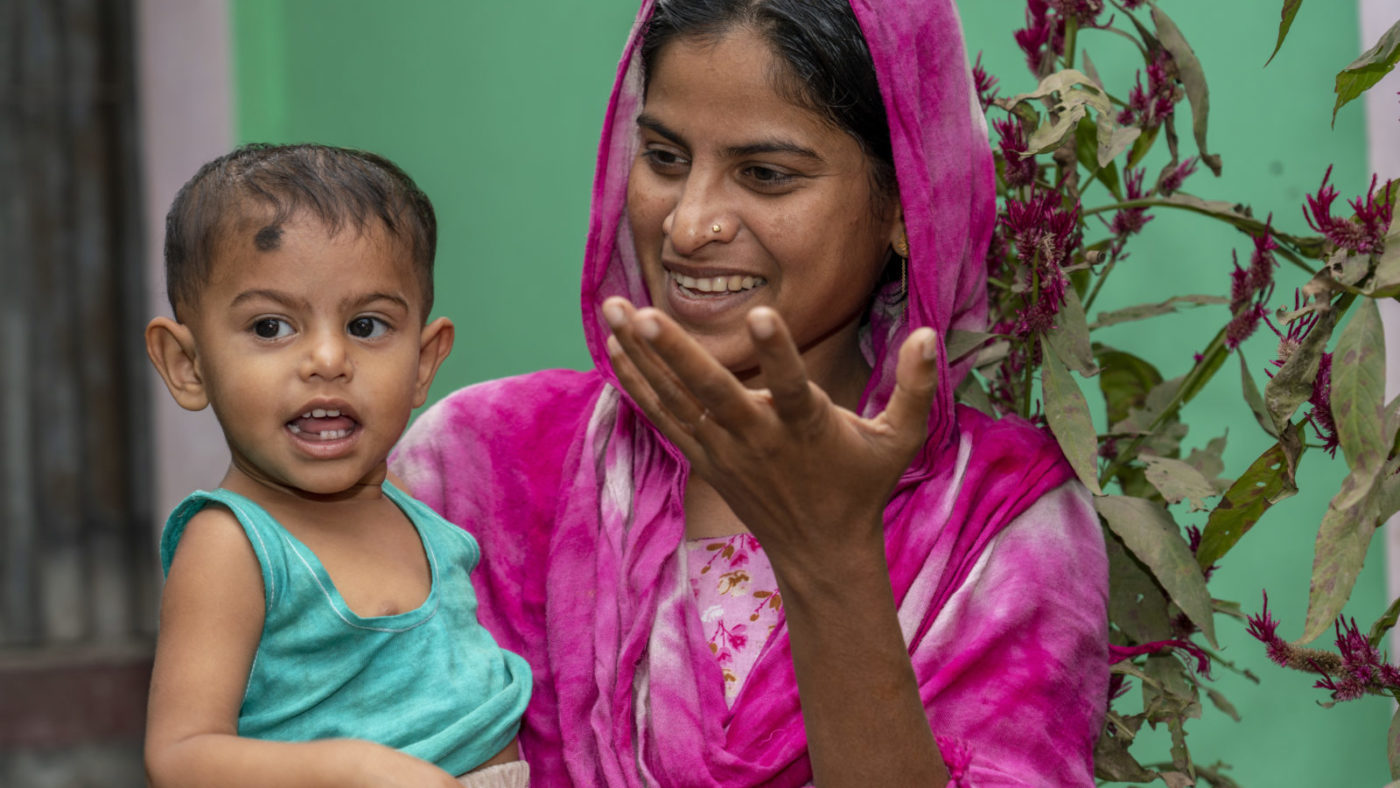 Shamima communicating with her young daughter via facial expressinons and hand signals. She wears a bright pink sari against a green backdrop.