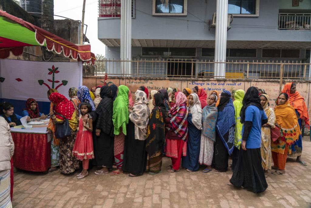 Women wait in line for eye screening tests.