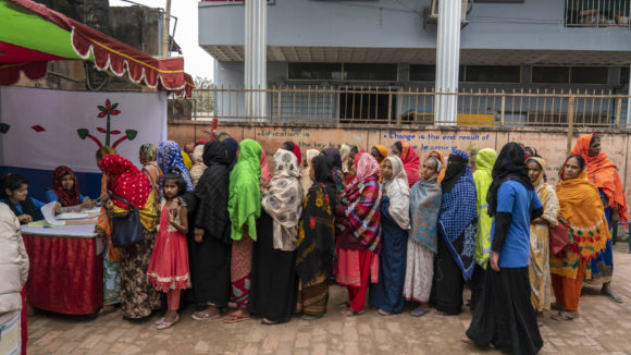 Women wait in line for eye screening tests.