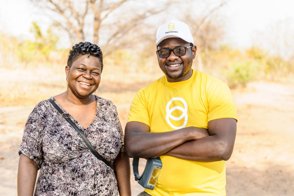 Givemore Mafukidze, wearing a Sightsavers tshirt, stands with Dr Agatha Aboe.