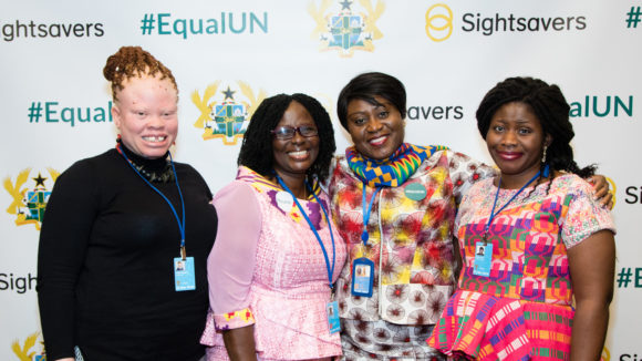 Four women standing together smiling, in front of a backdrop that says #EqualUN.