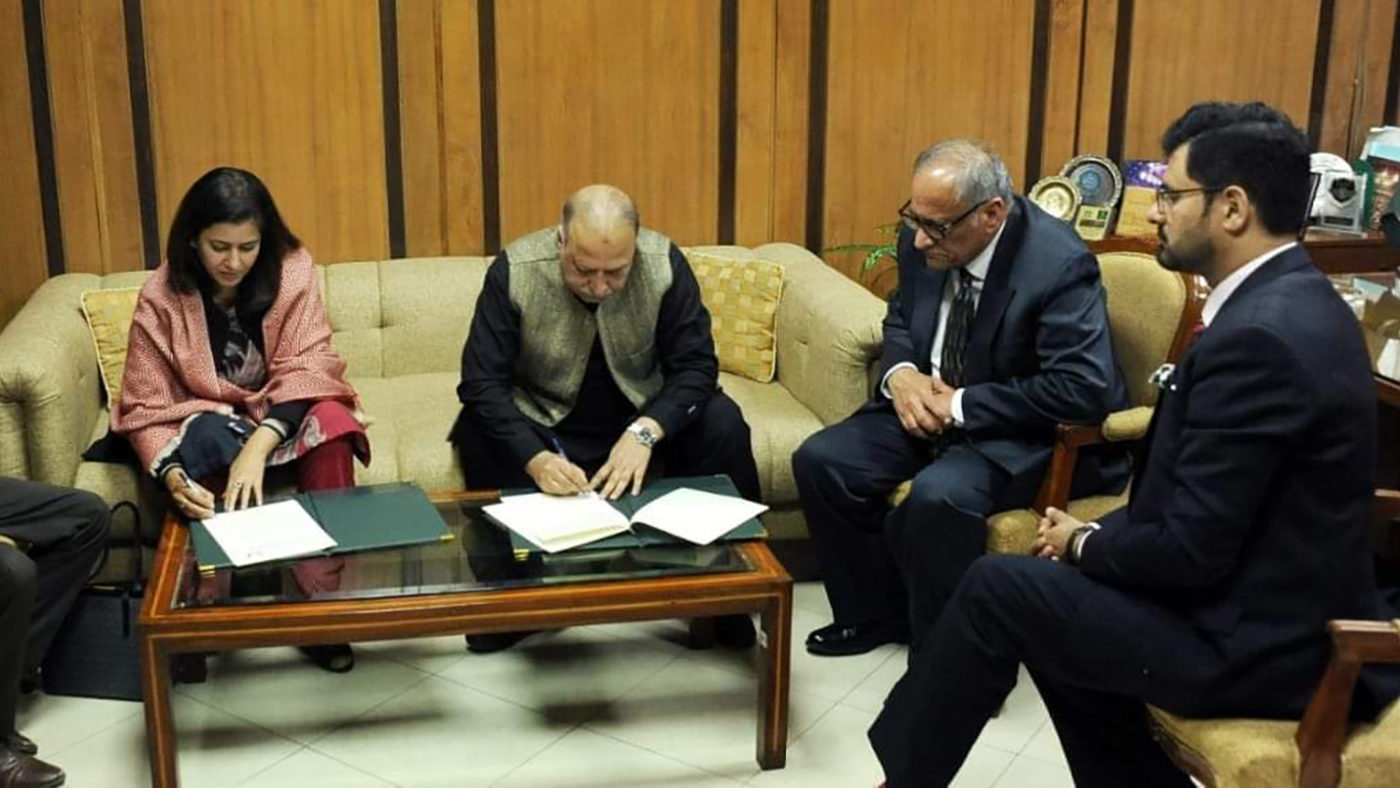 Four people sit in a room. Two of them are signing documents.