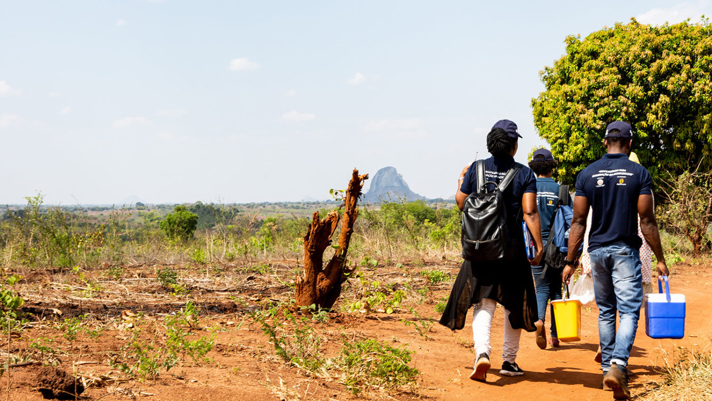 A group of people walking along a remote road. They are carrying buckets and coolers.