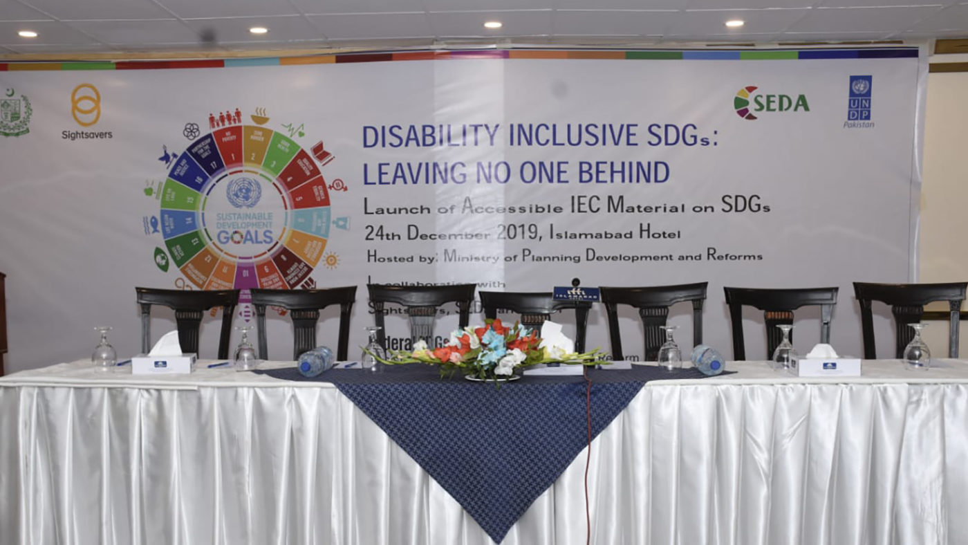 A table is laid out in front of a sign that says 'Disability Inclusive SDGs: Leaving no one behind'