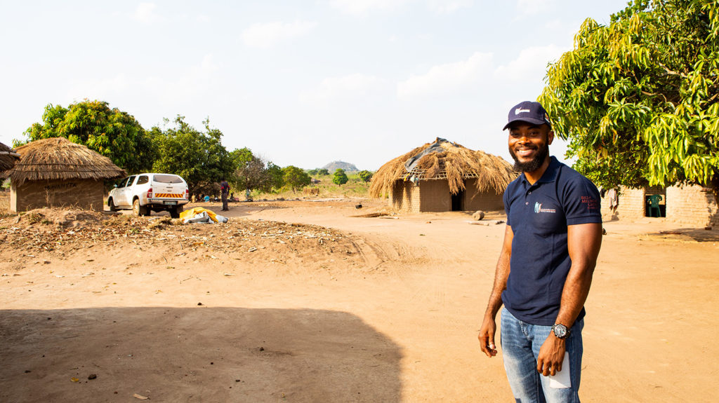 Clécio smiles as he stands in front of some homes.