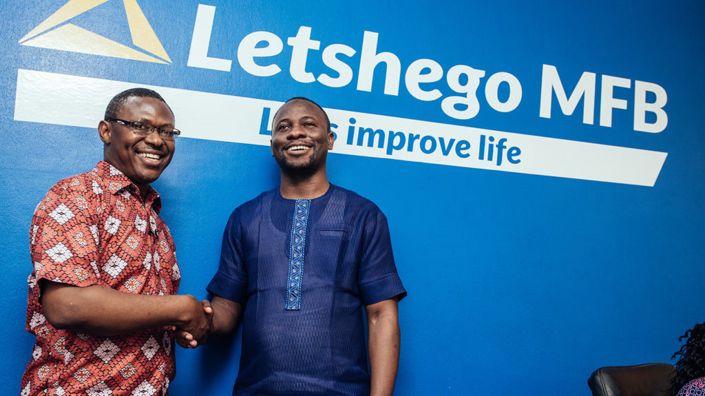 Two men shake hands in front of a sign for Letshego bank.