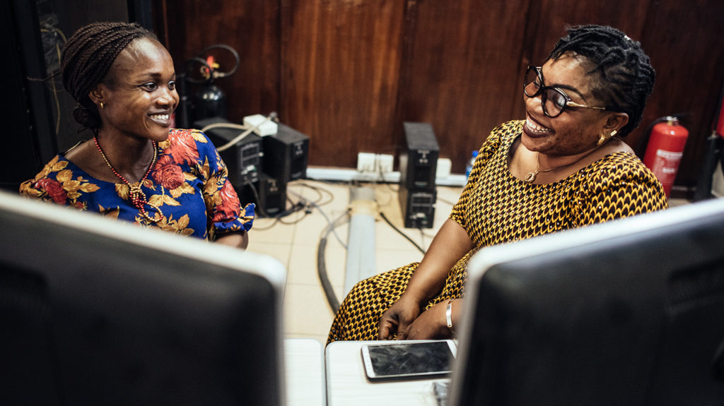 two women sit behind a computer, laughing.