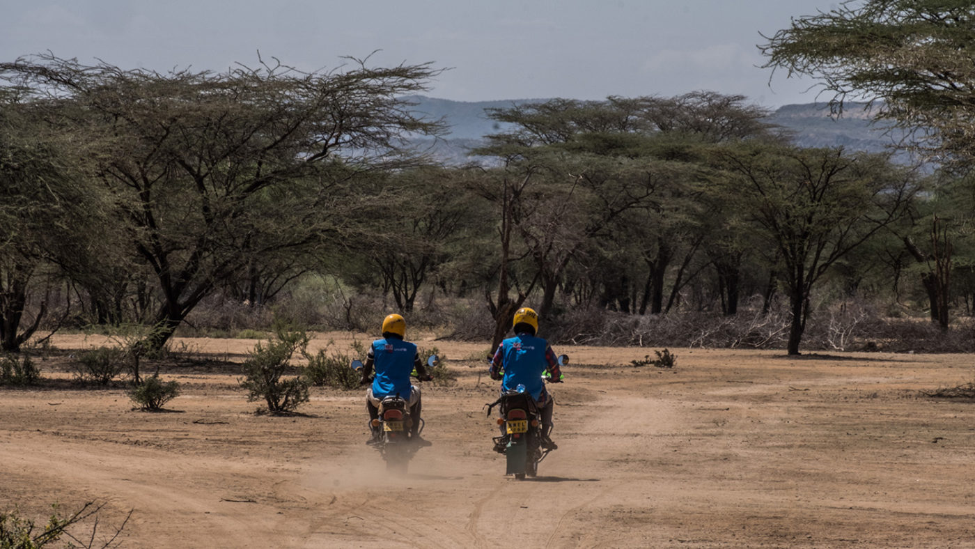 two volunteers ride motorbikes on a dirt road.