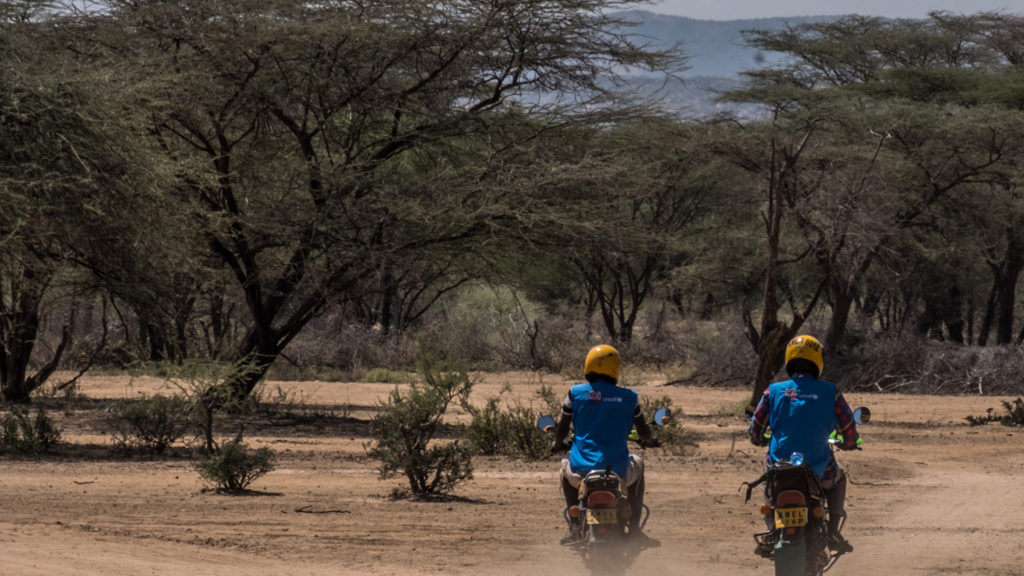 two men ride motorbikes down a dirt road.