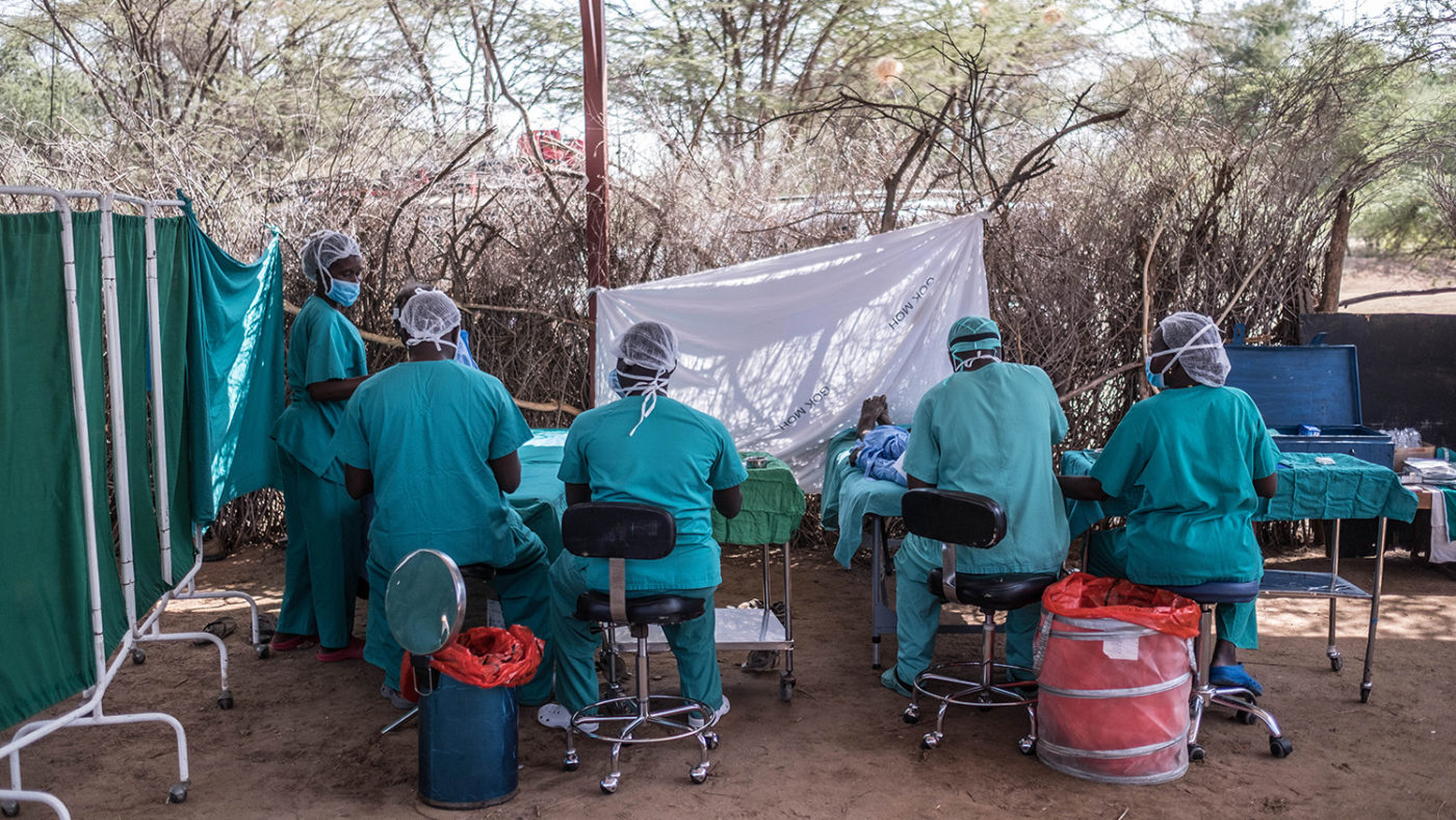A group of surgeons perform an operation outside under a tree.