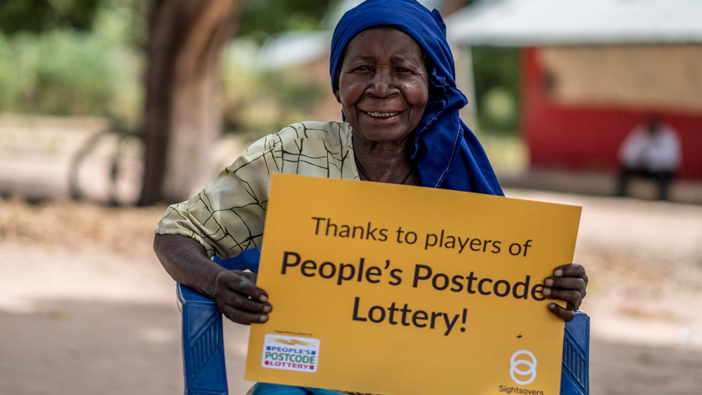 Aziza holds a sign saying 'Thanks to Players of People's Postcode Lottery'.