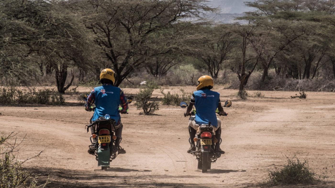 Two men riding motorcycles in rural Kenya.