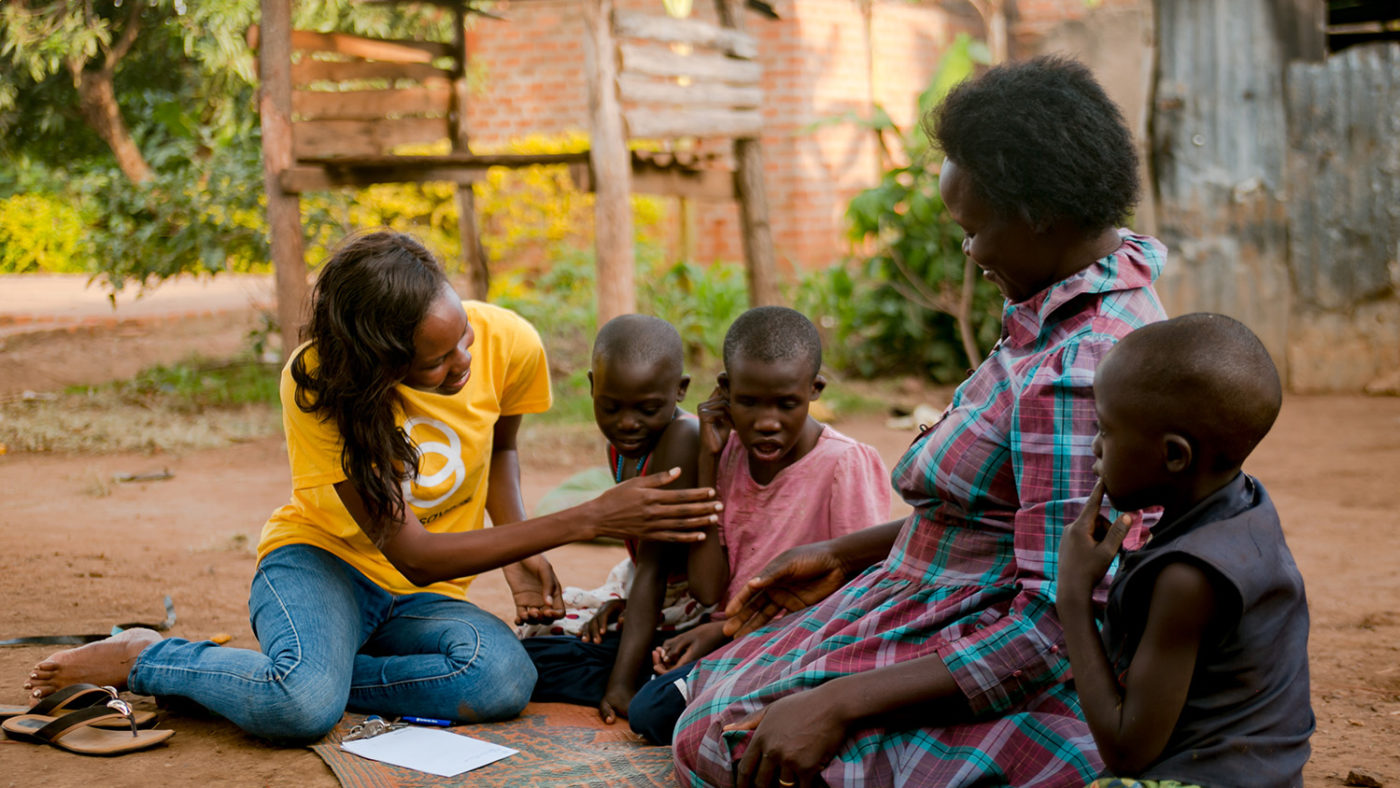 Sightsavers staff member Doreen sits with Hellen and her family,