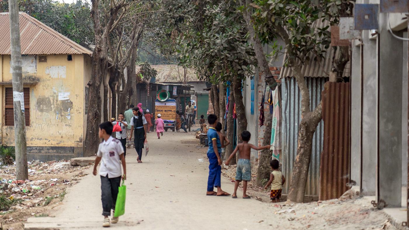 A miking tuk-tuk driving through a street in Bangladesh.