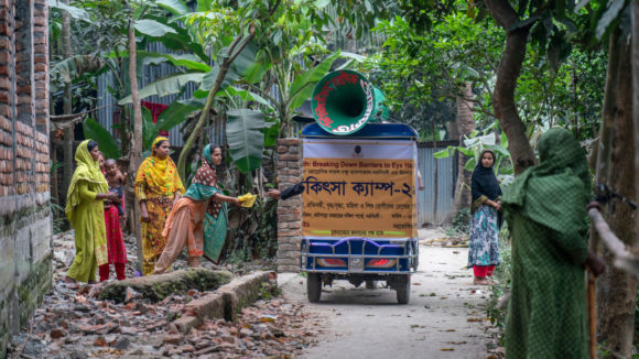 A tuk tuk passes a group of women.
