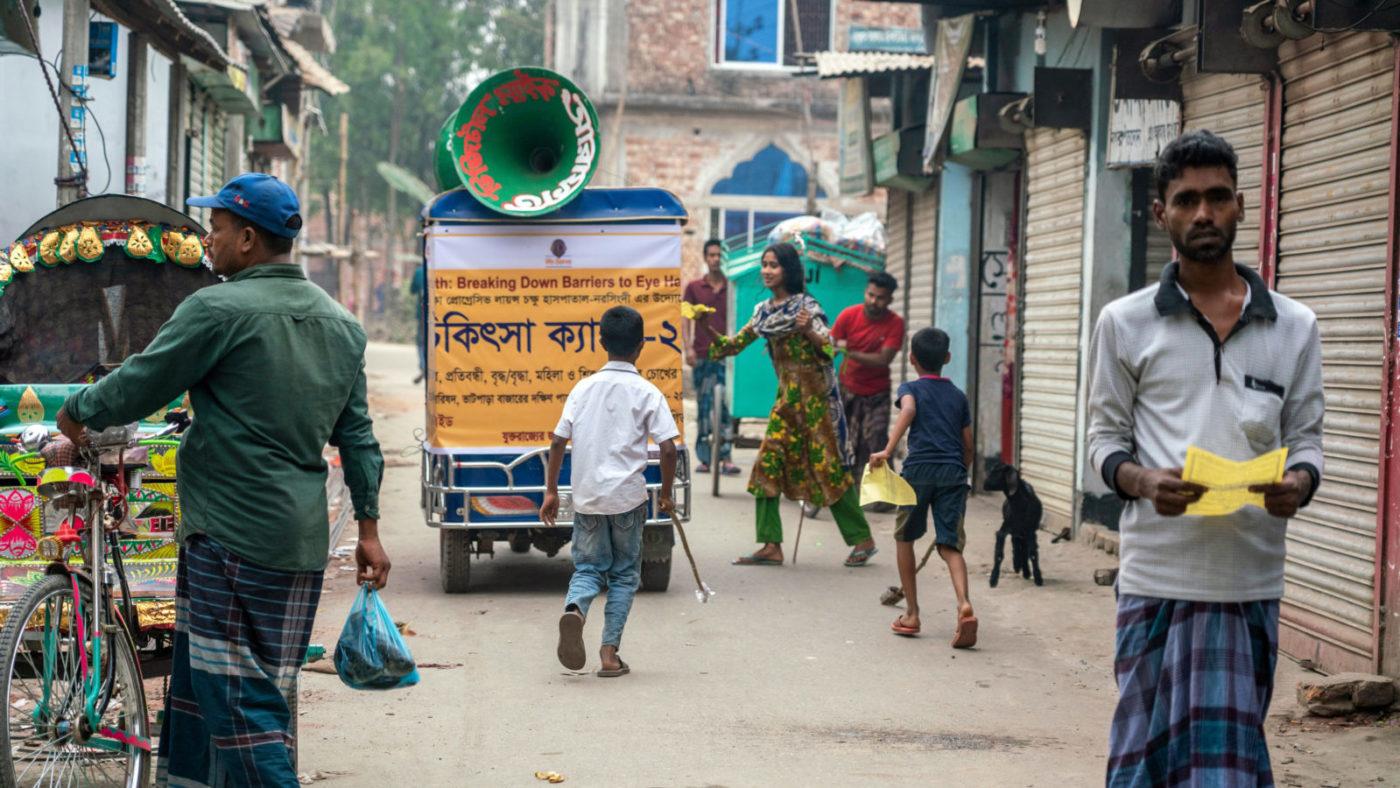 A miking tuk-tuk passes through a busy street.