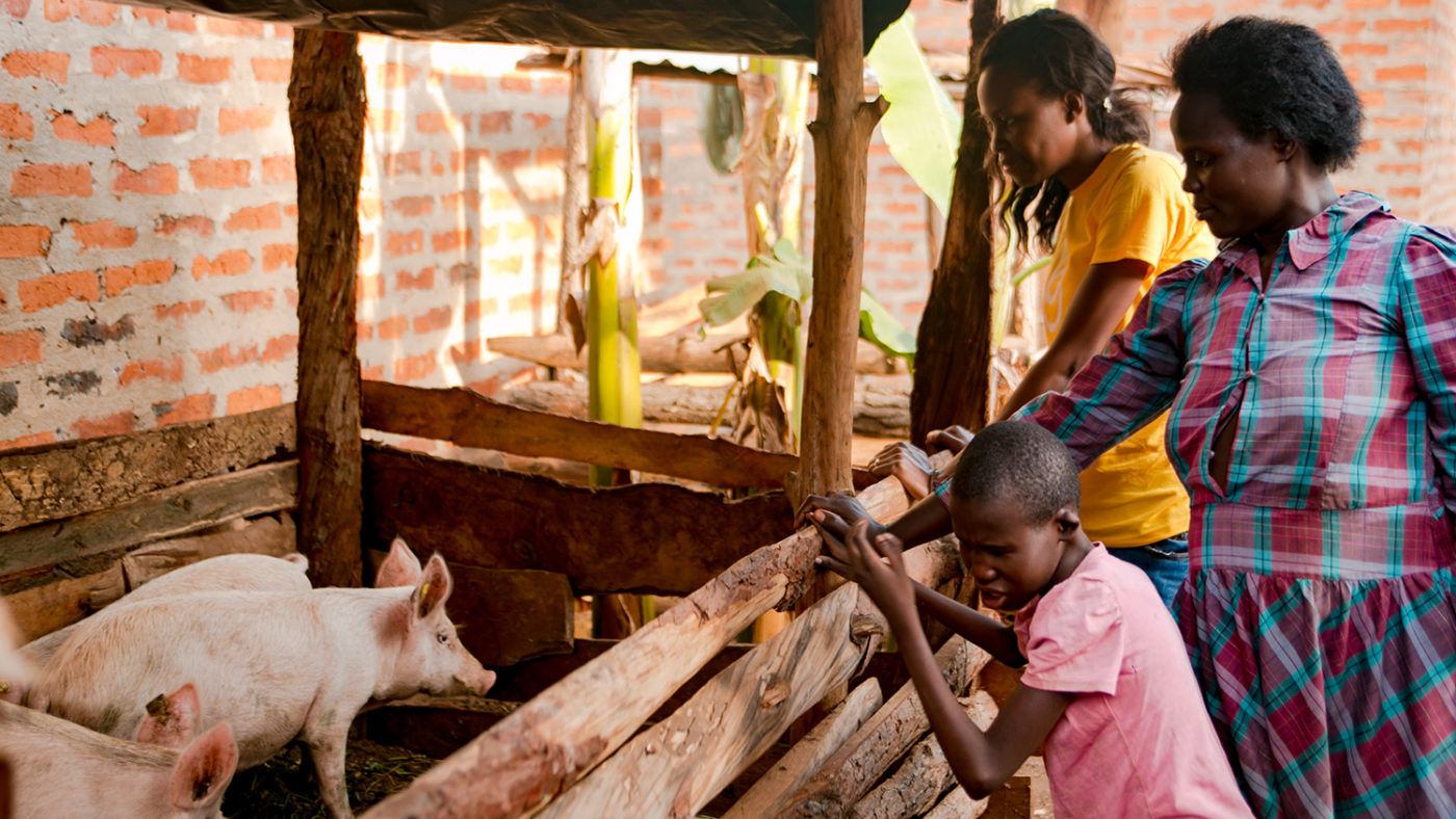 A Sightsavers worker stands with a mother and a child next to a pig pen.