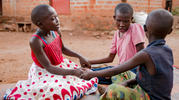 A girl with deafblindness plays with her siblings.