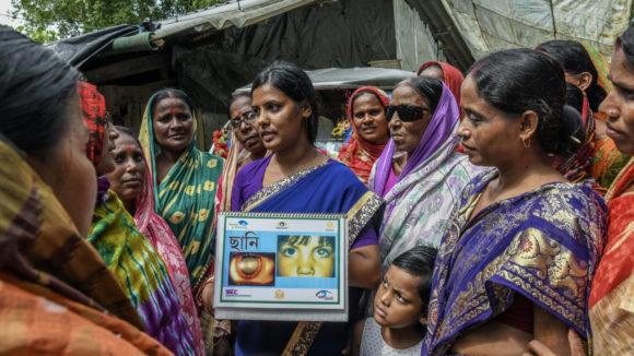 Women showing health information to a crowd.