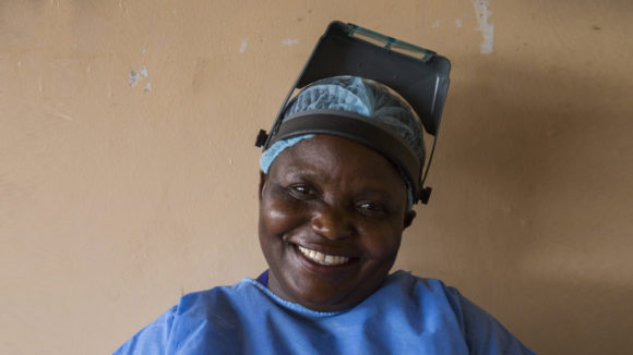 A woman smiling. She is dressed in surgical scrubs.