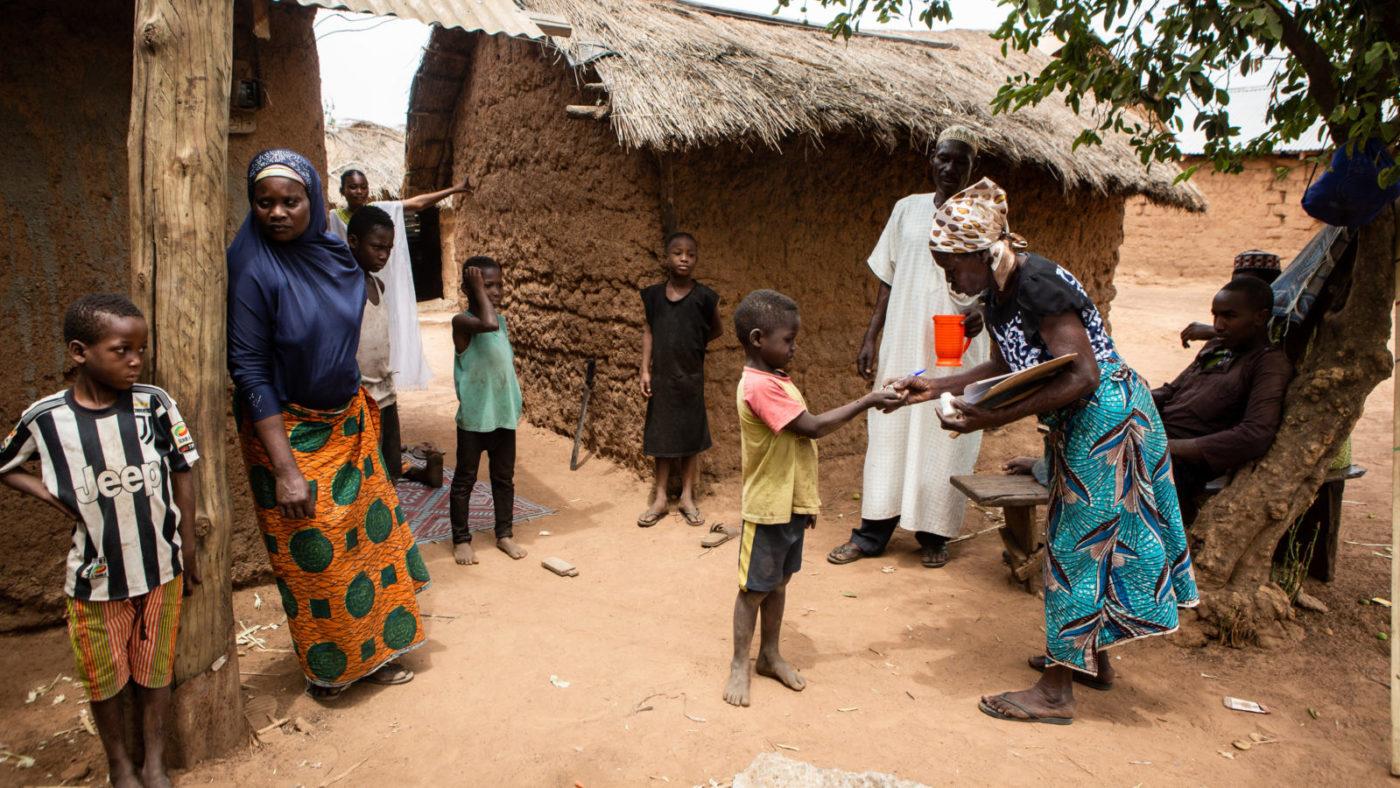 Women handing out medicine in a village.
